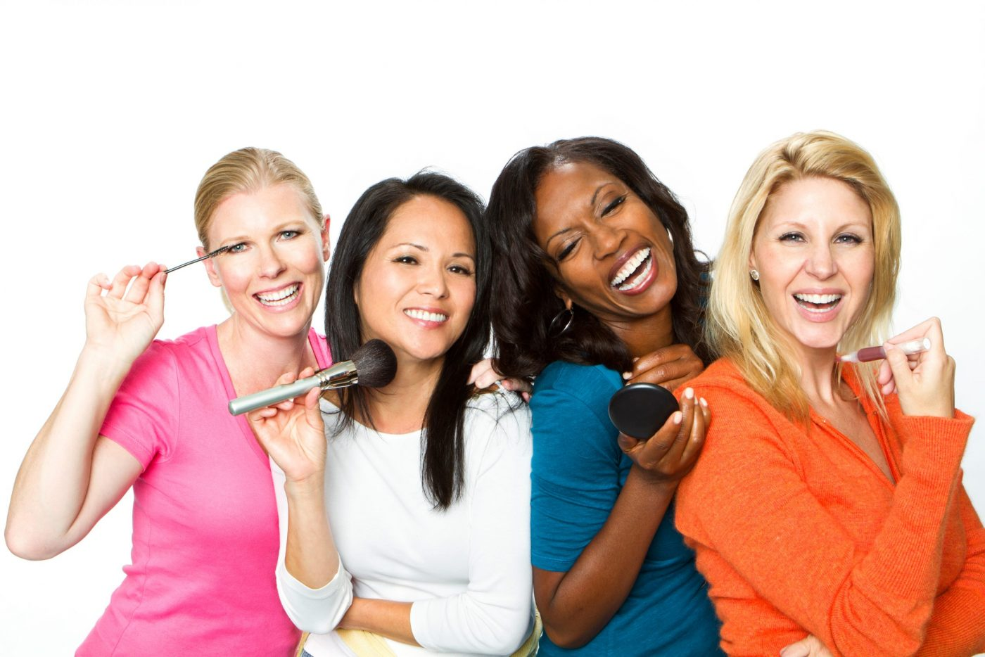 Diverse group of women putting on makeup
