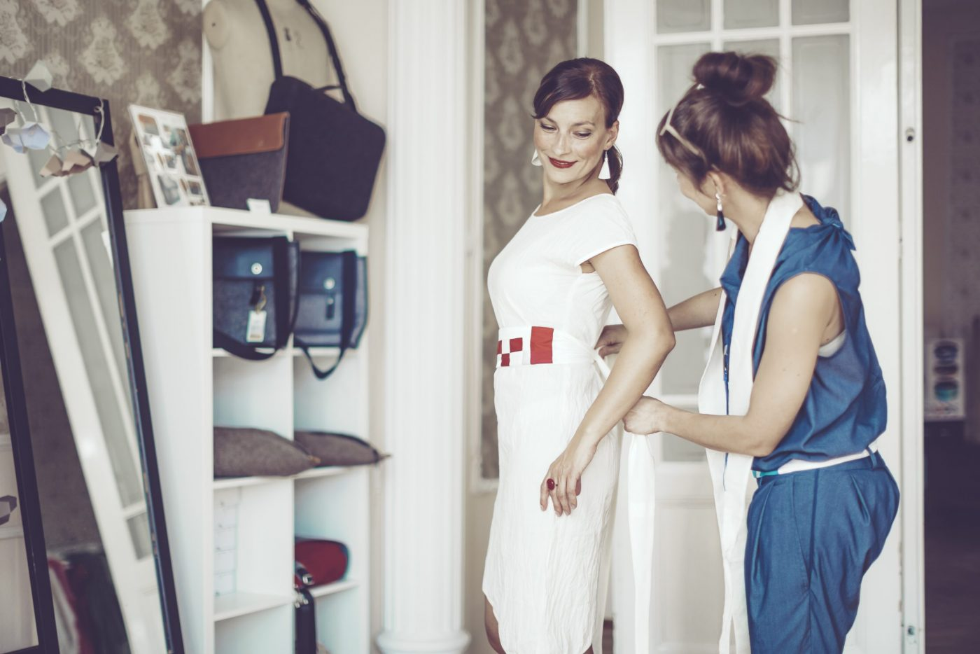 A fashion designer is helping her customer who is fitting on a new dress in the showroom. Candid shot.